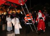 Weihnachtsengel und zahlreiche Zuschauer begrüßen den Weihnachtsmann
