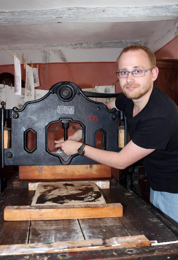 Matthias Gaertig stellt die Druckmaschine für die Probedrucke ein