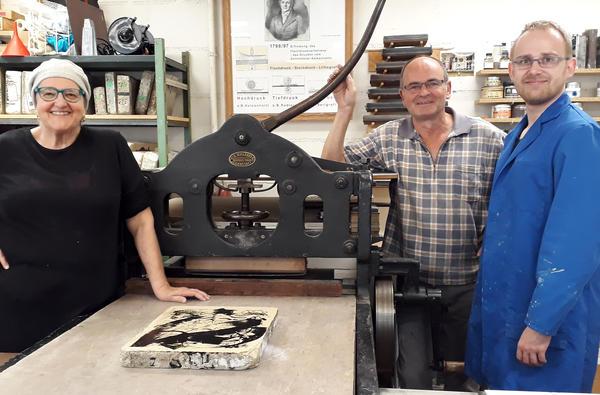 Angelika Flaig mit Michael Wackwitz und Matthias Gaertig (re.) in der Stuttgarter Litho-Werkstatt. Auf der Druckpresse der Haldensleber Stein.